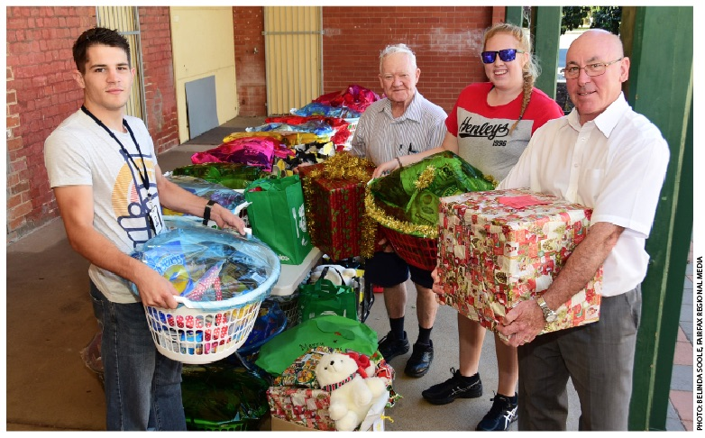 Four Vinnies volunteers with Christmas presents and hampers.