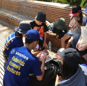 Vinnies youth wearing T-shirt with words 'Vinnies Renews, Rebuilds, Restores'.