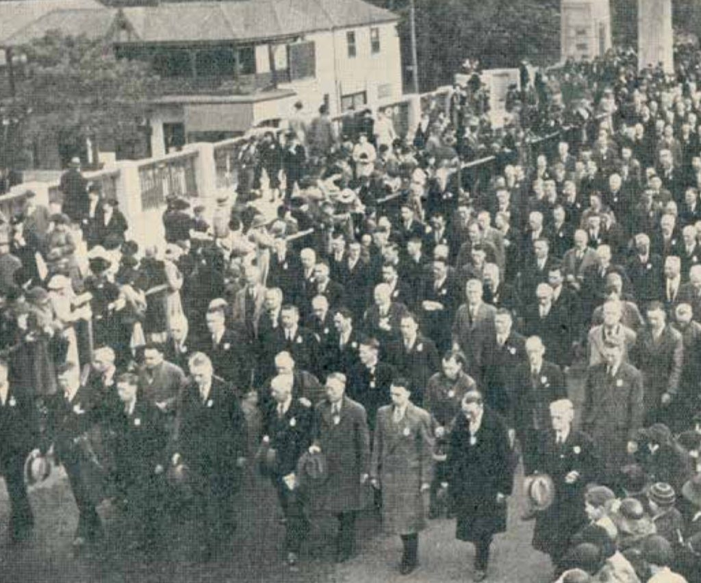 Black and white photo of crowd of men walking - they are dressed in suits or overcoats and carrying their hats.