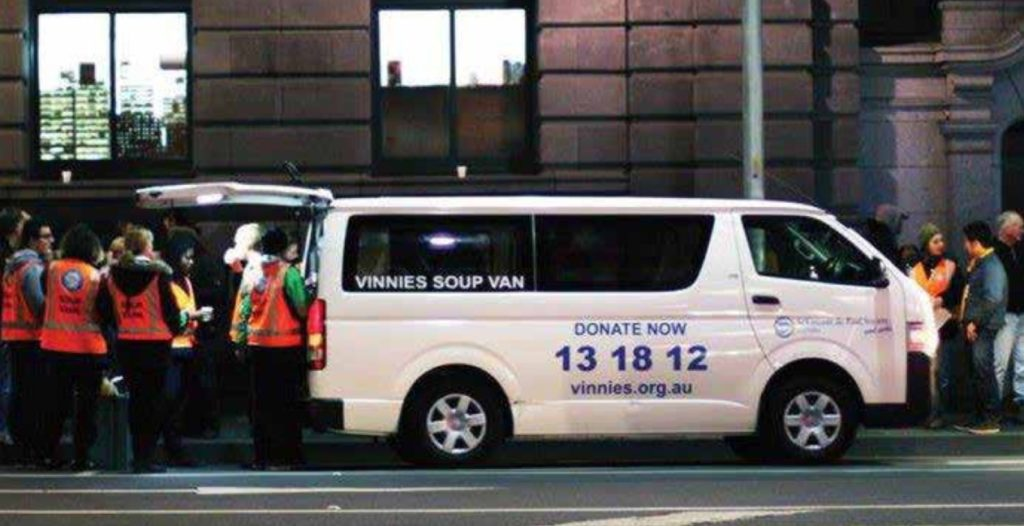 Vinnies Soup Van on a city street with people serving and receiving an evening meal.