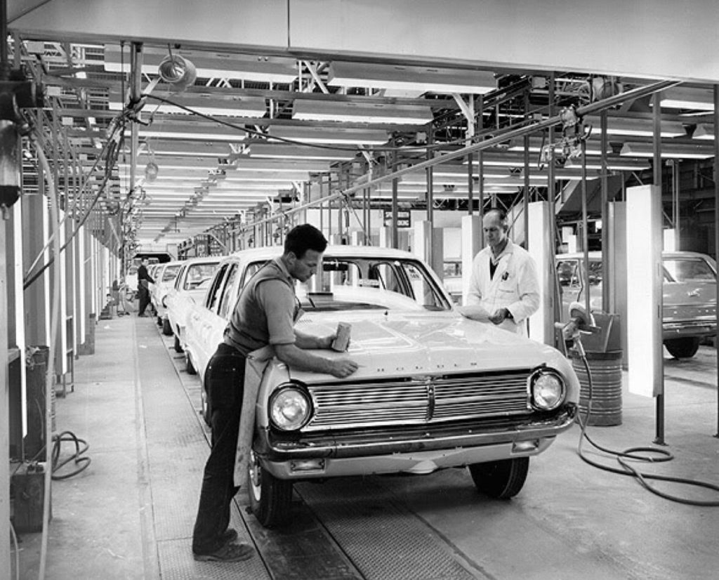 Image of the Holden assembly line. In the foreground a man finishing the front of the car. Another man in lab coat is on the other side of the car. A third worker can be seen in the distance down the line of cars.