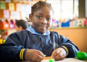 Young girl in school uniform at a table doing craft project.