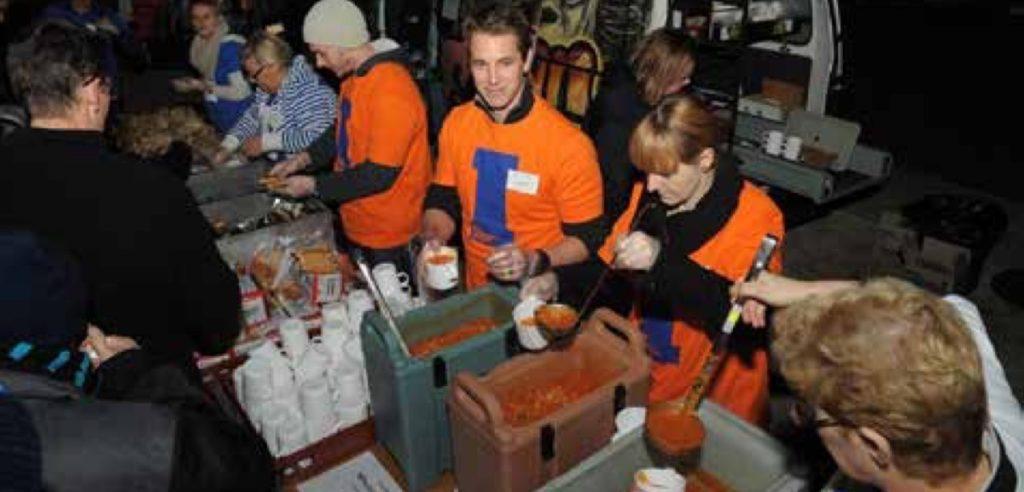 Vinnies workers serving food from a soup van.