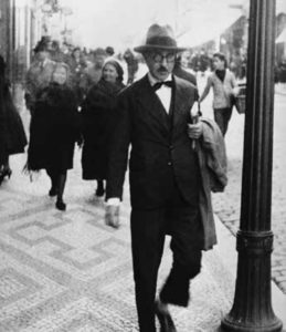 Street scene with man wearing a fedora in the foreground.