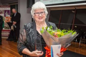 Woman holding a glass engraved award and bunch of flowers.
