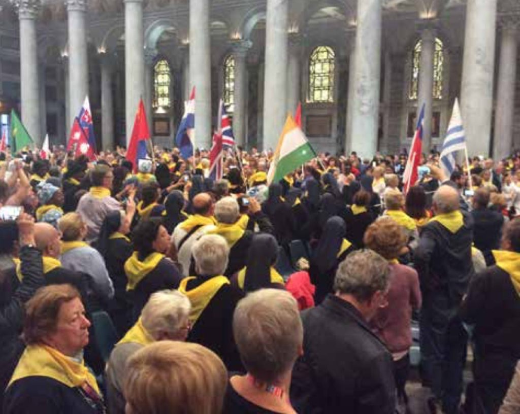A large group - hundreds of people - in front of the marble pillars of the basilica. Scattered throughout are the flags of different countries represented.