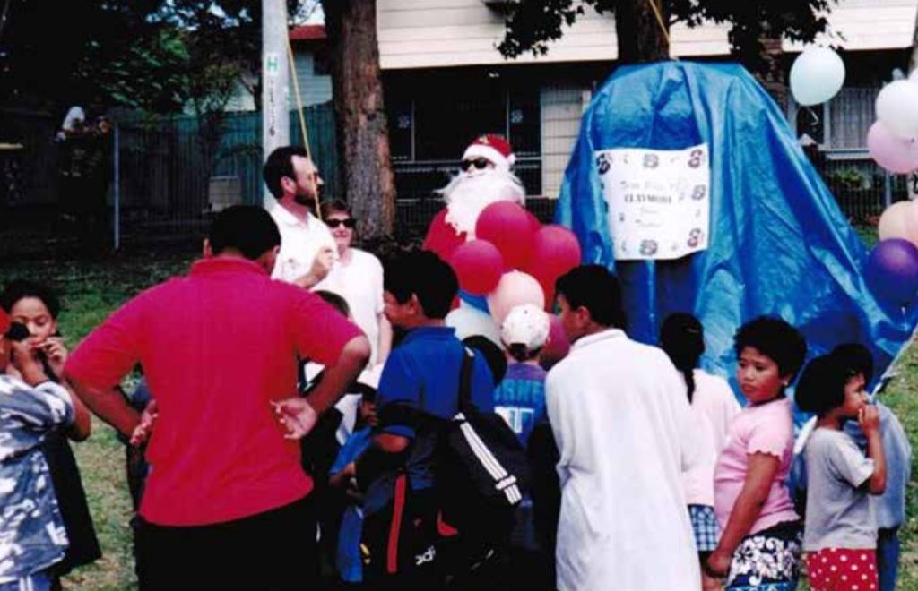 Children in a group with balloons and Santa in the background.