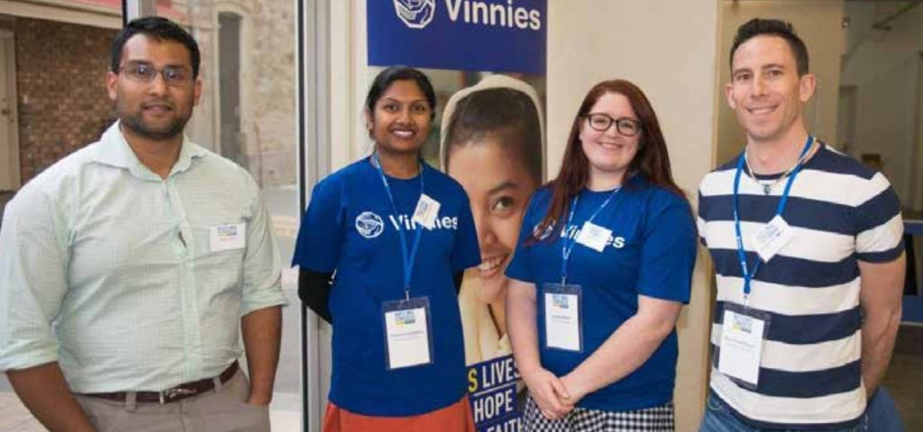 Four people standing in front of a poster that says 'Vinnies'.