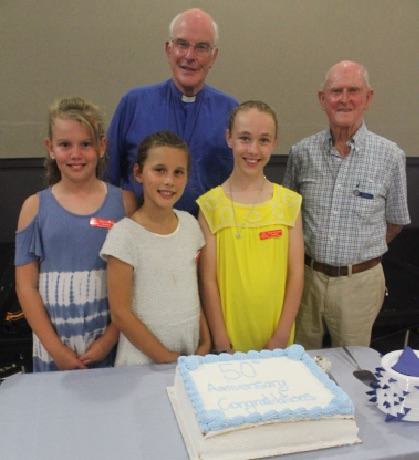 Bishop and group of Vncentians with large anniversary cake.