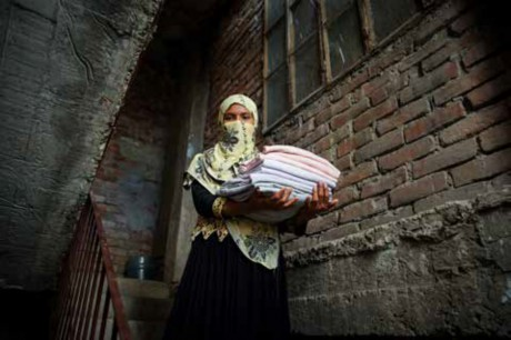 Image of woman wearing a hijab walking steps carrying a load of folded laundry.