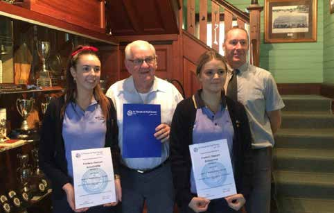 Image of four people at the foot of a staircase holding their certificates.