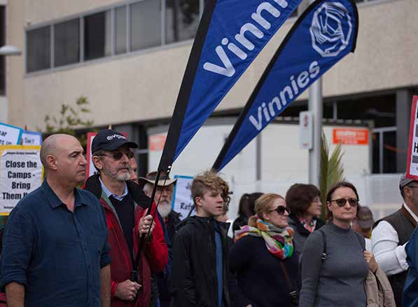 Group of people marching carrying Vinnies banners.