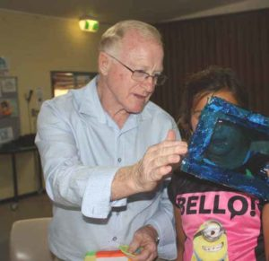 Bob Burns and a young girl looking at blue frame.