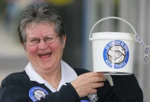Toni Muir holding up a plastic collection bucket.