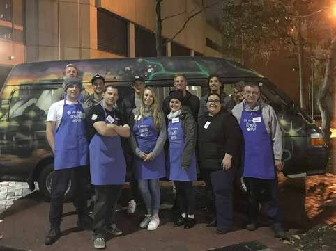 Group of people in blue aprons standing in front of Fred's Van.
