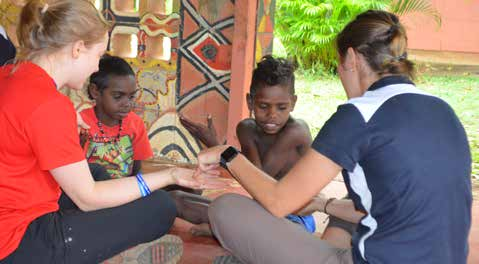 Ashley and another young woman sitting with two Aboriginal children.
