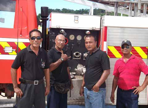 Four men standing in front of a red fire truck.