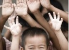 Thumbnail: small boy with his hands raised, the hands of others are in the background.