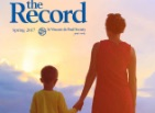 Thumbnail: The Record, woman and boy looking out towards a sky with sunlight breaking through clouds.