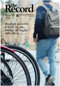 "The back of a man walking past bicycle tyres. ""Student poverty: a wall on the bridge of a higher education."""