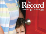 Thumbnail: The Record, a woman and small child in a doorway.