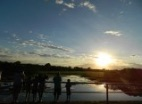 Thumbnail: people looking out over a marsh at sunrise.