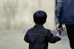 Small boy holding the hand of an adult.