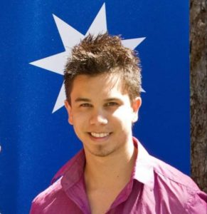 Young man standing in front of a poster with a white star.