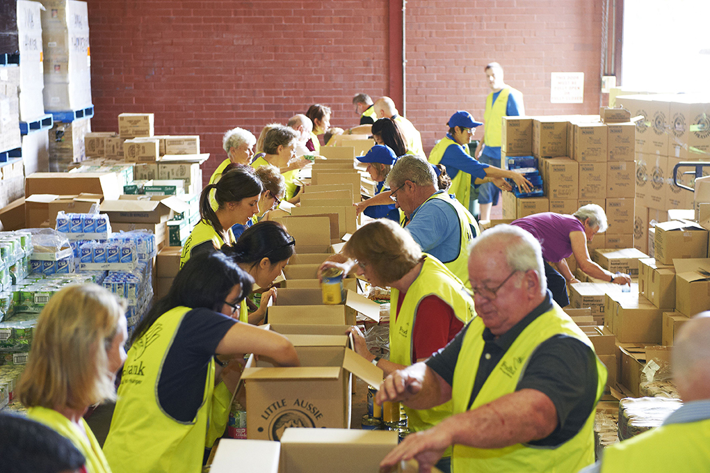Fifteen Vinnies workers in high-vis vests packing hamper boxes.