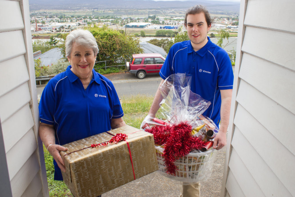 Two Vinnies workers with a large hamper and large gift box.
