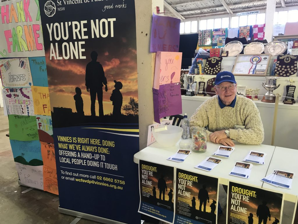 Man behind a table with brochures and a large poster: 'You're not alone'.