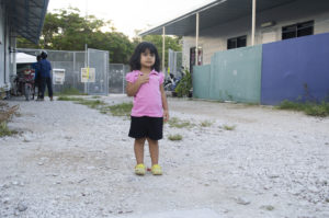 A small girl standing in a driveway.