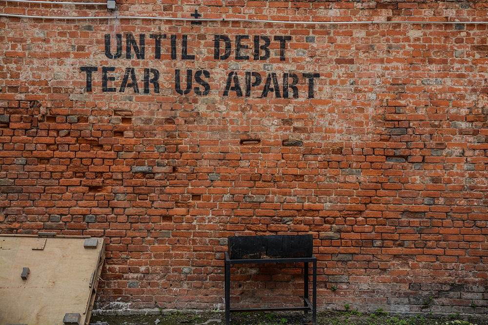 Brick wall with the words 'until debt tear us apart'.