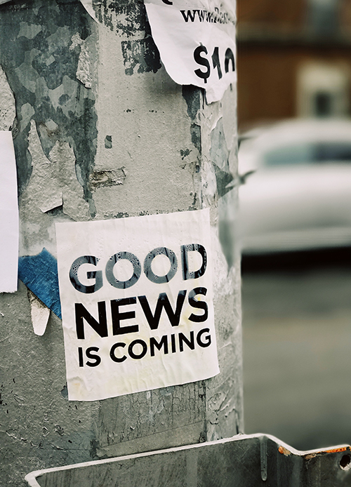 Poster on a street pole saying: Good news is coming.