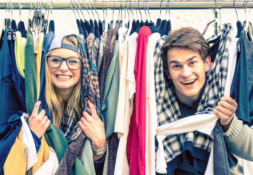 Two people looking through a rack of clothing.