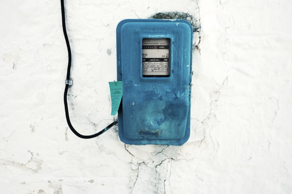 A blue electricity metre on a white wall.