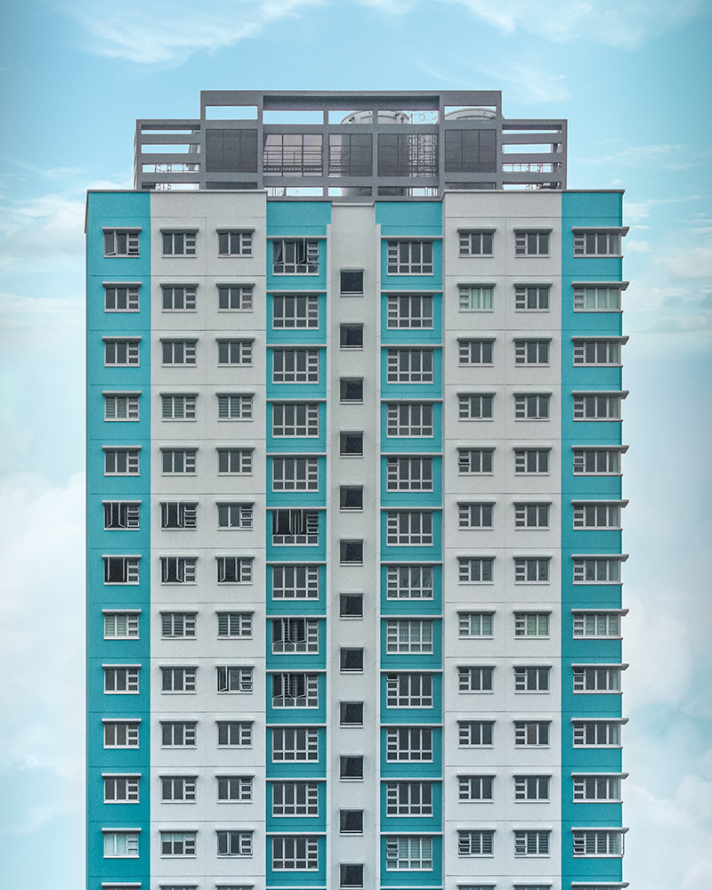 Tall apartment block with turquoise and white panels.