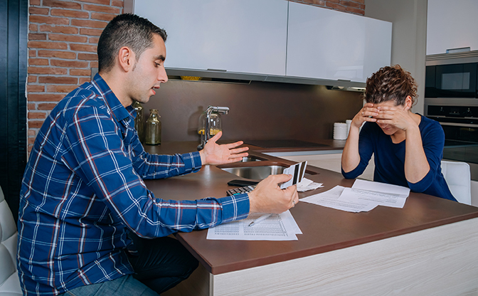 Young couple sitting on either side of a kitchen bench struggling with documents.