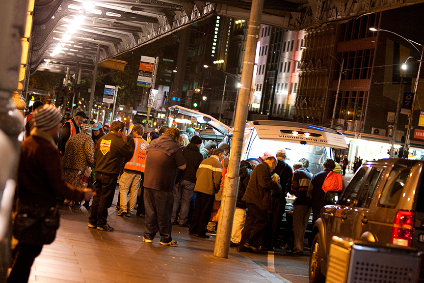 People crowding around a soup van at night on a city street.