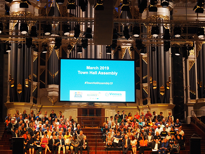 Large group in town hall with very large pipe organ in the background. A projected slides above their heads says 'March 2019 Town Hall Assembly'.