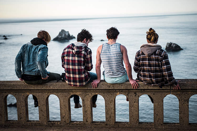 Four young people with their backs to the camera sitting on a railing looking out over the sea.