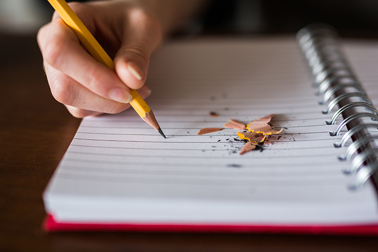 A hand holding a pencil above a blank notebook page with shavings lying on the page.