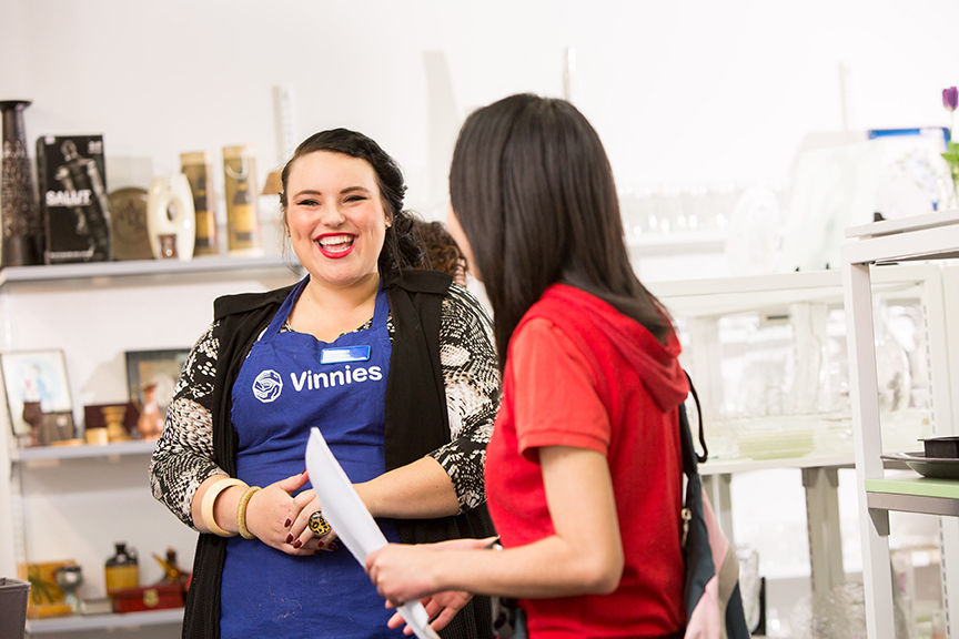 Two women in a shop, one wearing a blue Vinnies T-shirt.
